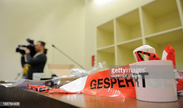 A scotch tape that reads 'offlimits' lies on a desk in a courtroom of the Regional Court of Munich southern Germany on March 15 where the trial...