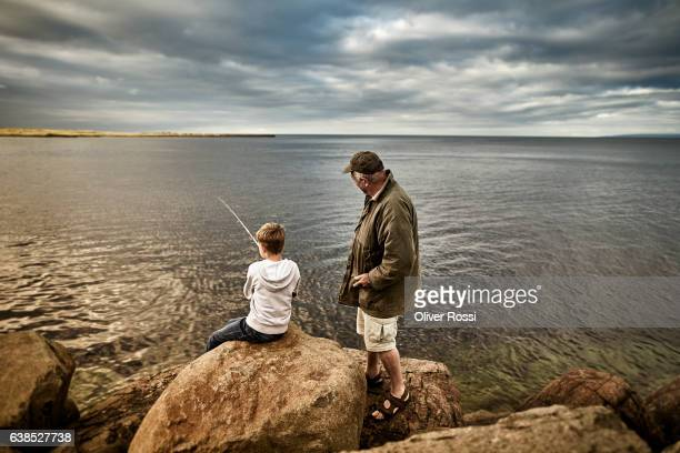 uk, scotland, boy and senior man fishing together - fishing industry stock pictures, royalty-free photos & images
