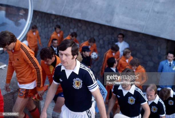 Scotland captain Bruce Rioch is followed by Stuart Kennedy as he leads his team out alongside Ruud Krol and the Dutch team prior to the FIFA World...