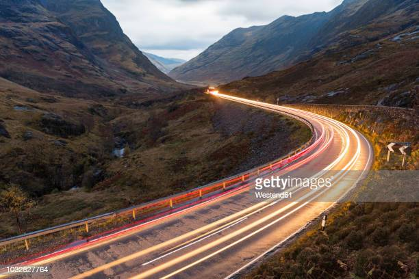 uk, scotland, car light trails on scenic road through the mountains in the scottish highlands near glencoe at dusk - long exposure stock pictures, royalty-free photos & images