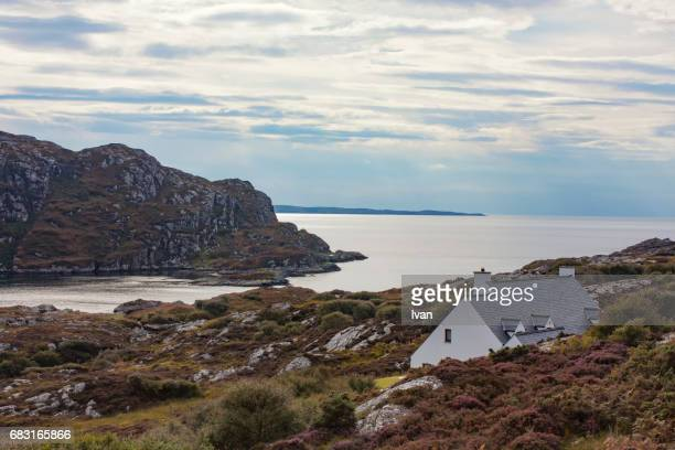 scotland crofters cottage in dramatic highland mountain glen panorama - schotland stockfoto's en -beelden