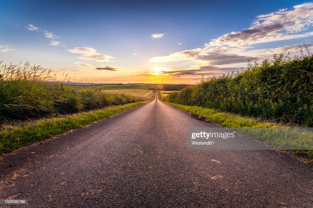 UK, Scotland, East Lothian, empty country road at sunset : Stock Photo