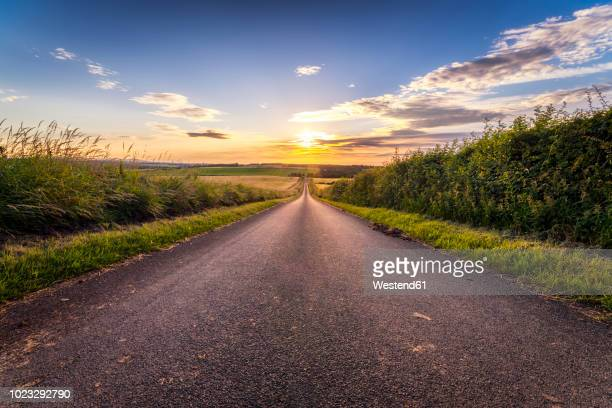 UK, Scotland, East Lothian, empty country road at sunset