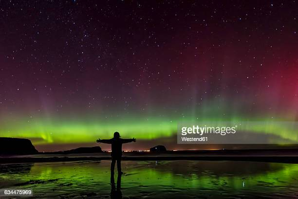 Scotland, East Lothian, silhouette of woman standing on Seacliff Beach watching Northern lights