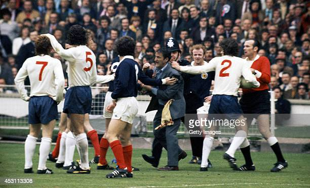 Scotland fan is restrained by a policeman after attempting to reach England player Alan Ball during a Home International Championships match between...
