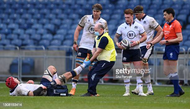 Scotland forward Grant Gilchrist receives treatment from Doctor James Robson wearing PPE during the Guinness Six Nations match between Scotland and...