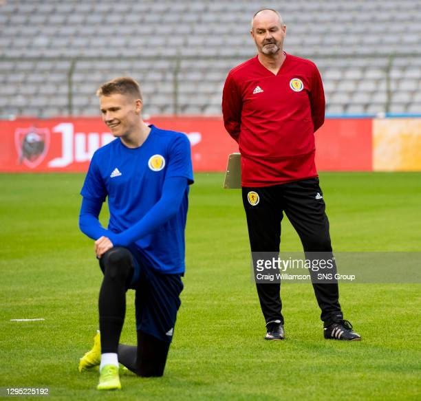 Scotland head coach Steve Clarke watches on as Scott McTominay warms up .