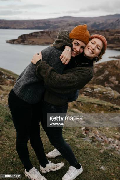 uk, scotland, highland, happy female friends hugging in rural landscape - weibliche freundschaft stock-fotos und bilder