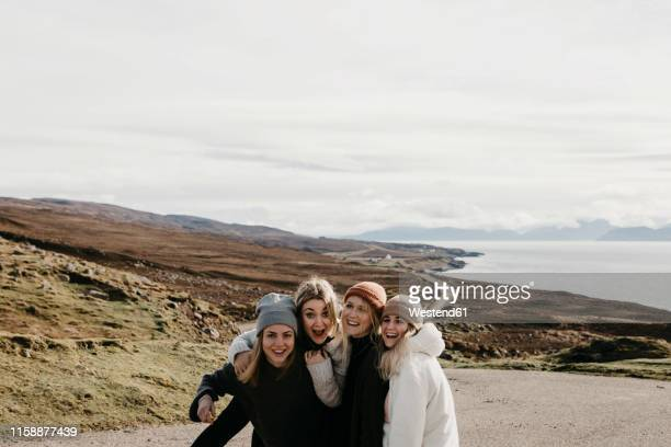 uk, scotland, highland, happy female friends on a road at the coast - outdoors stock pictures, royalty-free photos & images