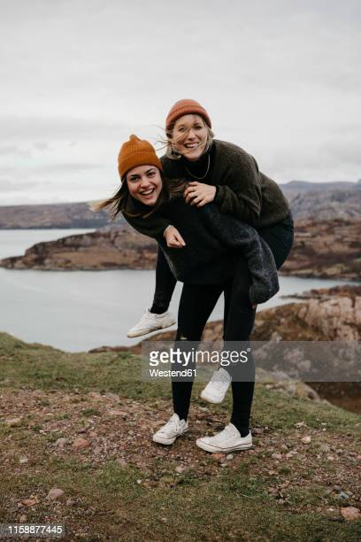 uk, scotland, highland, happy woman carrying friend piggyback in rural landscape - knit hat stock pictures, royalty-free photos & images