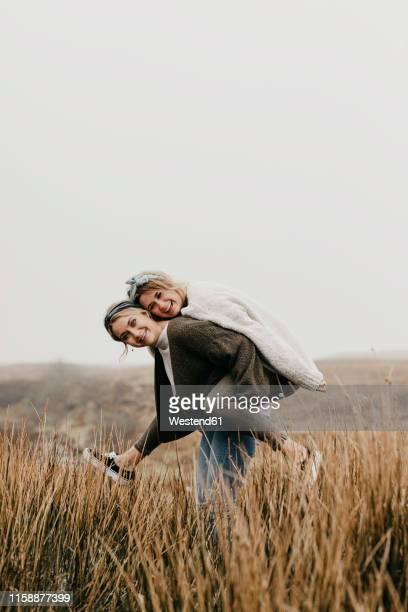 uk, scotland, isle of skye, happy woman carrying friend piggyback in rural landscape - 25 29 jahre stock-fotos und bilder