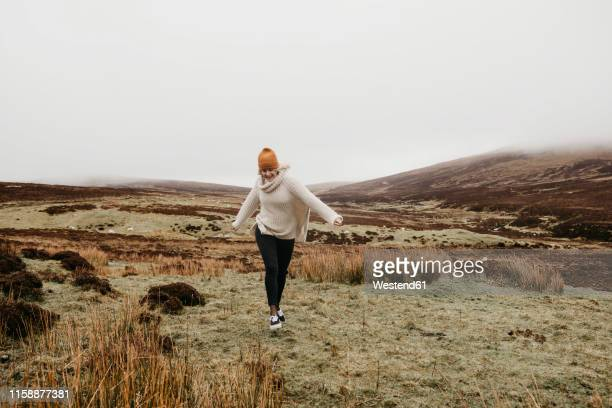 uk, scotland, isle of skye, happy young woman running in rural landscape - ポートリー ストックフォトと画像
