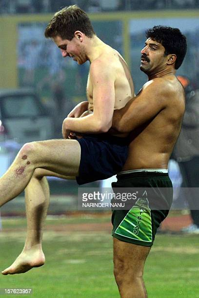 Scotland kabaddi player is tackled by his Pakistani opponent during the 3rd Pearls World Cup Kabaddi Punjab2012 tournament at Guru Nanak Stadium in...