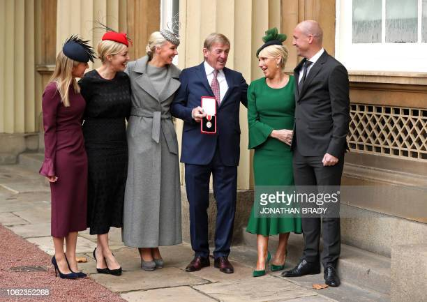 Scotland Liverpool football club legend Kenny Dalglish holds his medal as he poses for a photograph with daughters Lauren Dalglish Kelly Cates and...