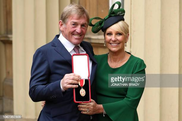Scotland Liverpool football club legend Kenny Dalglish holds his medal as he poses for a photograph with his wife Marina after being knighted as a...