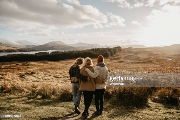 uk, scotland, loch lomond and the trossachs national park, rear view of female friends looking at view - arm around stock pictures, royalty-free photos & images