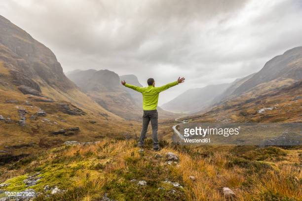 uk, scotland, man in the scottish highlands near glencoe with a view on the three sisters - freedom stock pictures, royalty-free photos & images