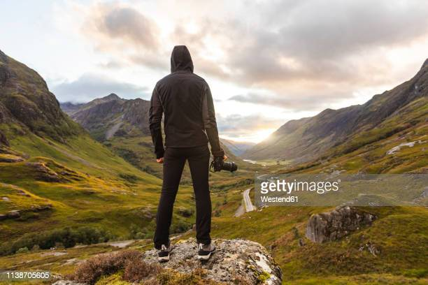 uk, scotland, man looking at view with the three sisters of glencoe mountains on the left and the a82 road in the middle of the valley - black jacket stock pictures, royalty-free photos & images