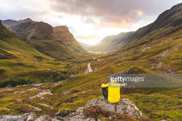 uk, scotland, man looking at view with the three sisters of glencoe mountains on the left and the a82 road in the middle of the valley - tal stock-fotos und bilder