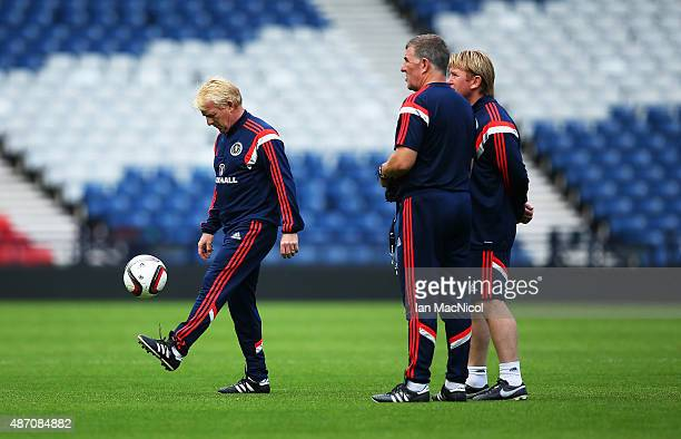Scotland manager Gordon Strachan controls the ball as his assistants Mark McGhee and Stuart McCall look on during a training session ahead of their...