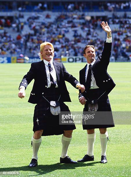 Scotland players Colin Hendry and Kevin Gallacher wave to fans whilst wearing their kilts before the opening FIFA 1998 World Cup match between Brazil...