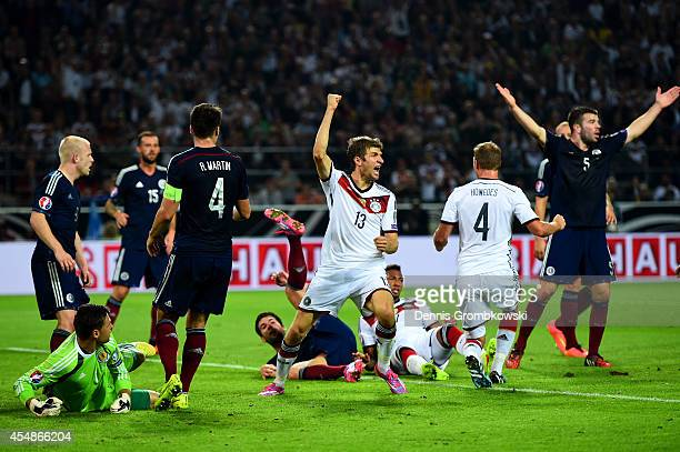 Scotland players react as Thomas Mueller of Germany celebrates scoring their second goal during the EURO 2016 Group D qualifying match between...
