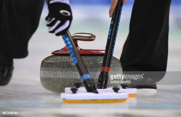 Scotland players sweep ahead of the stone during their play-off against Sweden at the Women's Curling World Championships in Beijing on March 25,...