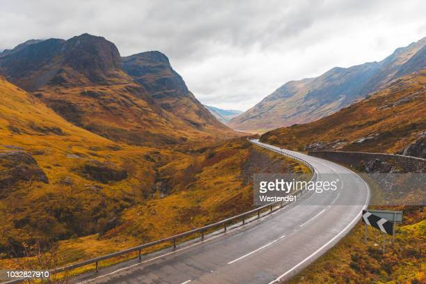 uk, scotland, scenic road through the mountains in the scottish highlands near glencoe with a view on the three sisters - glencoe scotland stock pictures, royalty-free photos & images