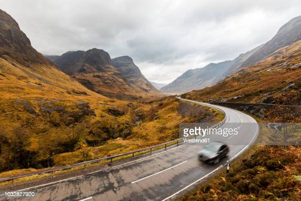 uk, scotland, scenic road through the mountains in the scottish highlands near glencoe with a view on the three sisters - country road stock photos and pictures