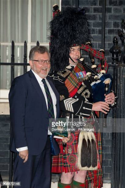 Scotland Secretary David Mundell poses for a photo with a piper of the Scots Guards outside 10 Downing Street Westminster London to welcome guests to...
