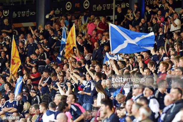 Scotland supporters wave flags in the crowd ahead of the group F World Cup qualifying football match between Scotland and England at Hampden Park in...
