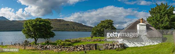Scotland traditional thatched croft cottage beside Highland loch