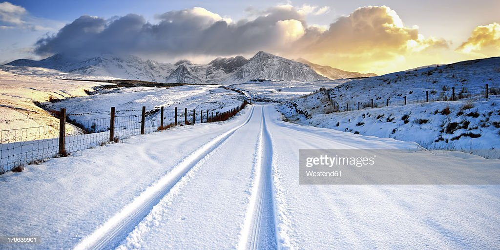 UK, Scotland, View of tyre track and snow mountains : Stock Photo