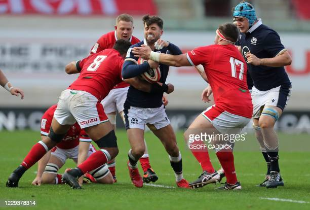 Scotland's Adam Hastings tries to break a tackle from Wales' number 8 Taulupe Faletau and Wales' Wyn Jones during the 2020 Six Nations Championship...