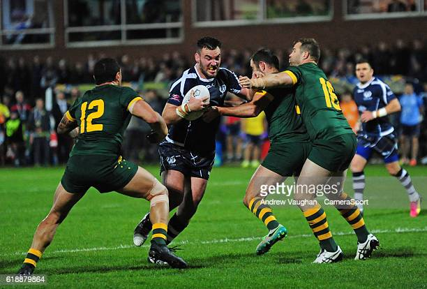 Scotland's Adam Walker is tackled by Australia's Tyson Frizell Australia's Cameron Smith and Australia's Trent Merrin during the Four Nations match...