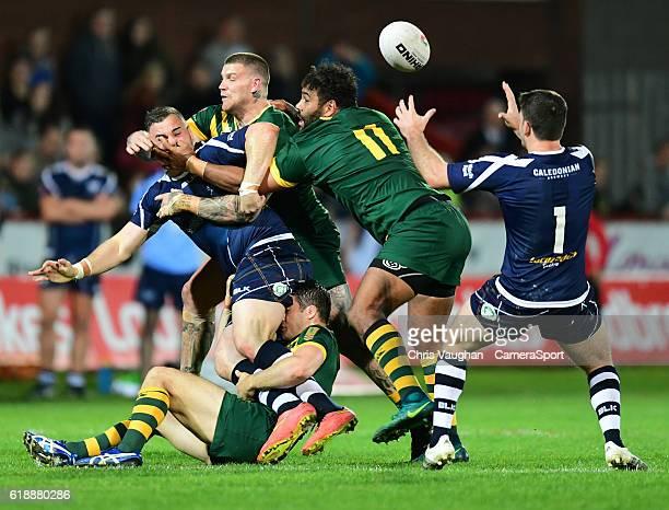 Scotland's Adam Walker offloads the ball to teammate Adam Walker under a challenge from Australia's Cooper Cronk Australia's Josh Dugan and...