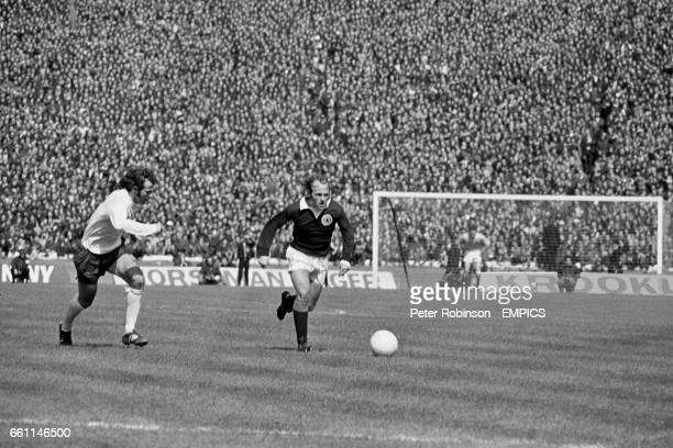 Scotland's Archie Gemmill carries the ball forward as England's Peter Storey pursues