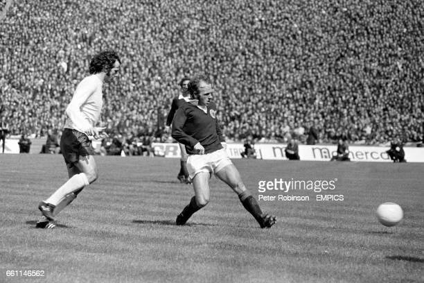Scotland's Archie Gemmill lays the ball off watched by England's Peter Storey