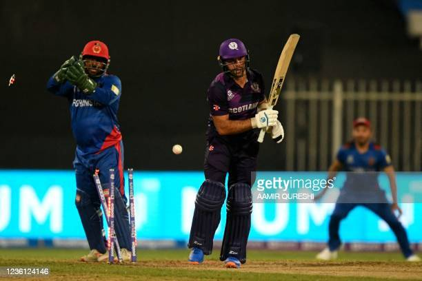 Scotland's captain Kyle Coetzer is clean bowled by Afghanistan's Mujeeb Ur Rahman as Afghanistan's wicketkeeper Mohammad Shahzad watches during the...