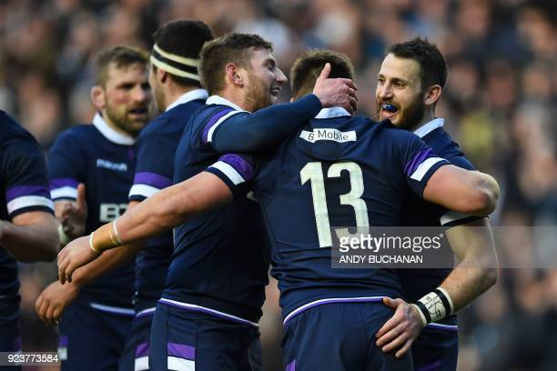 Scotland's centre Huw Jones celebrates with teammates after scoring their first try during the Six Nations international rugby union match between...
