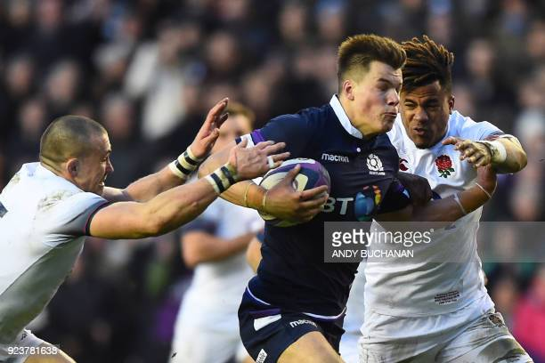 Scotland's centre Huw Jones runs in Scotland's third try as England's wing Anthony Watson and England's fullback Mike Brown try to stop him during...
