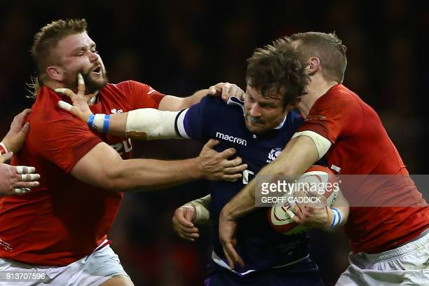 TOPSHOT Scotland's centre Pete Horne is tackled by Wales' Tomas Francis and Wales' centre Hadleigh Parkes during the Six Nations international rugby...