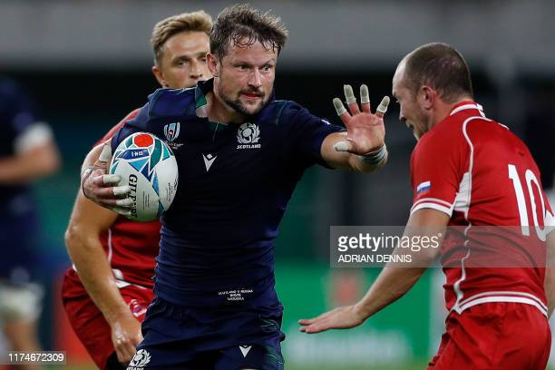 Scotland's centre Peter Horne fends off a tackle by Russia's flyhalf Ramil Gaisin during the Japan 2019 Rugby World Cup Pool A match between Scotland...