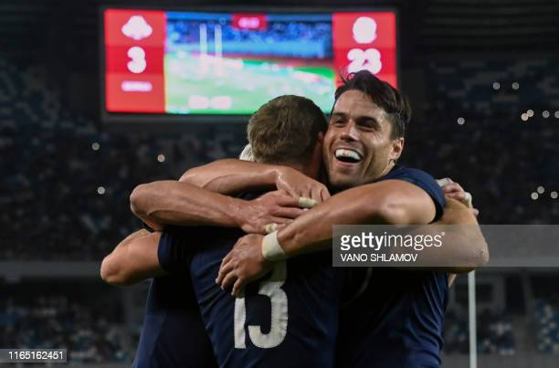Scotland's centre Rory Hutchinson is congratulated by teammates including winger Sean Maitland after scoring a try during the international rugby...