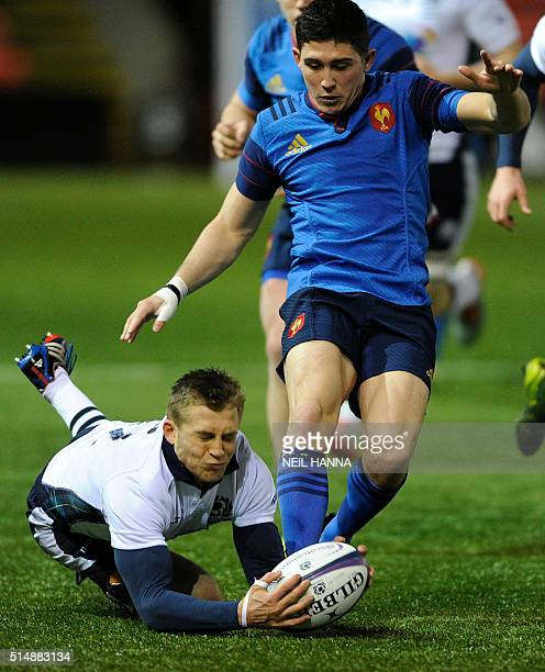 Scotland's centre Tom Galbraith dives for the ball in front of France U20's fly-half Anthony Belleau during a men's Under 20, 6 Nations rugby union...