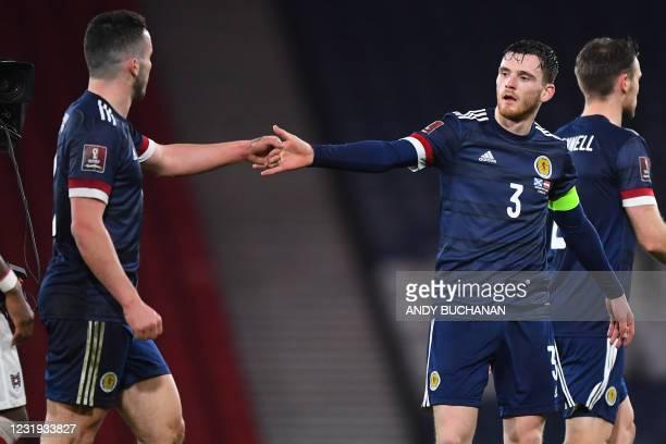 Scotland's defender Andrew Robertson congratulates Scotland's midfielder John McGinn on the pitch after the FIFA World Cup Qatar 2022 qualification...