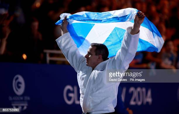 Scotland's Euan Burton celebrates winning gold over Pakistan's Shah Hussain Shah in their Men's 100kg contest at the SECC during the 2014...