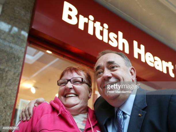 Scotland's First Minister Alex Salmond poses for a phone photo with a voter outside the British Heart Foundation charity shop in the East Kilbride...