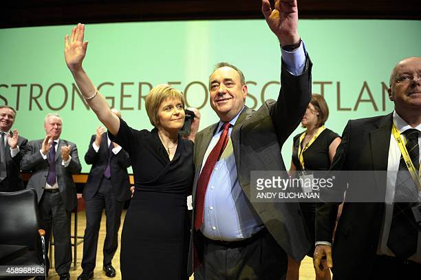 Scotland's First Minister Alex Salmond waves together with new party leader Nicola Sturgeon as he delivers his final speech as the leader of the...