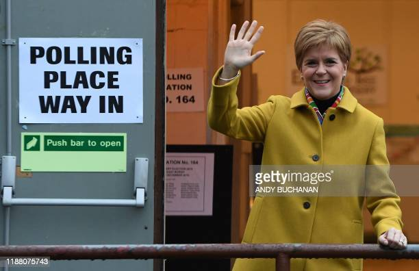 Scotland's First Minister and leader of the Scottish National Party Nicola Sturgeon waves outside a Polling Station where she arrived to cast her...